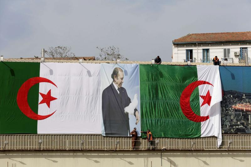 Algerian city employees install national flags and a poster of President Abdelaziz Bouteflika on a street in Algiers.