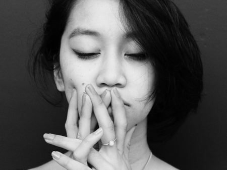 A woman in black and white holds her hands to her face with her eyes closed