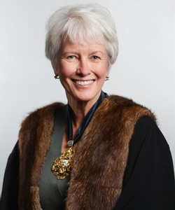 Annie smiles facing the camera wearing a black robe with fake fur brown trim and wearing a badge of the Merchant Taylors' crest
