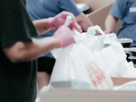 a foodbank where in foreground a person in black top and pink gloves holds distribute white plastic bags of food