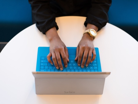 A woman of colour types on a tablet's blue keyboard on a white circular table