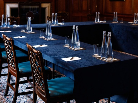 A blue tablecloth and items set up on tables for a meeting