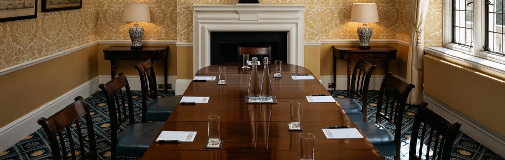 A boardroom table is set up for a meeting with pens and papers on the table