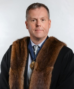 Richard looks straight-on into the camera wearing a pale blue shirt and the MT badge with a faux-fur trimmed black robe