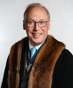 Duncan wears a light blue tie and a brown faux fur trimmed black robe