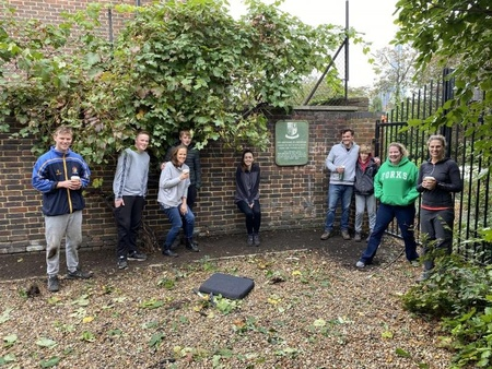 A group of people, socially distanced stand in a garden