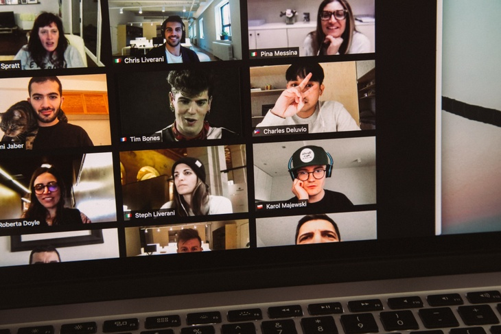 A laptop screen shows a number of young people on a Zoom call