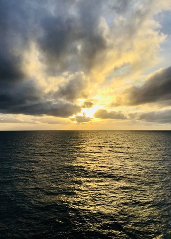 A dark sea borders the bottom image with a bright sun shines through gathering clouds