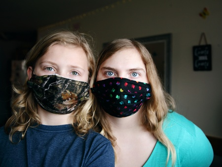 A woman and child look into the camera wearing dark, patterned masks