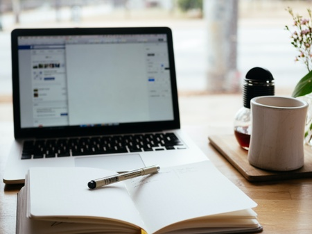A notebook and pen are placed in front of a laptop with a cup of tea beside it on a desk