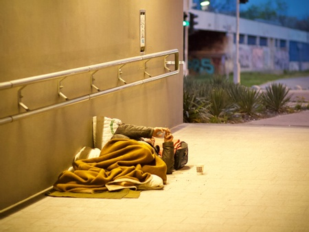 In a lit tunnel, a person lies in a makeshift bed of brown blankets facing up and with their arms raised are using a phone