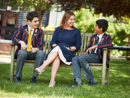 Two smiling young male pupils sit beside a female teacher on a bench