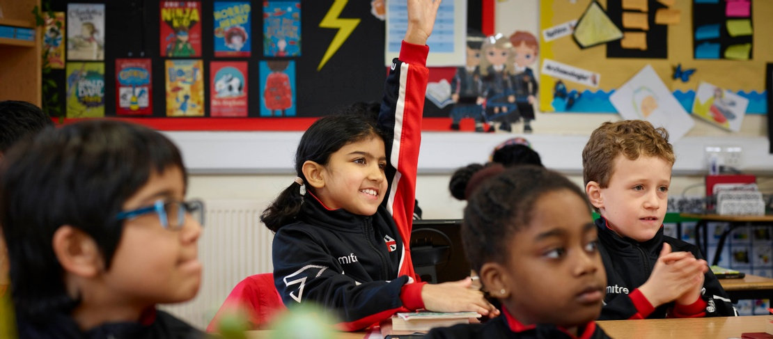 A young girl in a school classroom of peers puts her hand up to answer a question. She looks excited and is wearing a black and red tracksuit