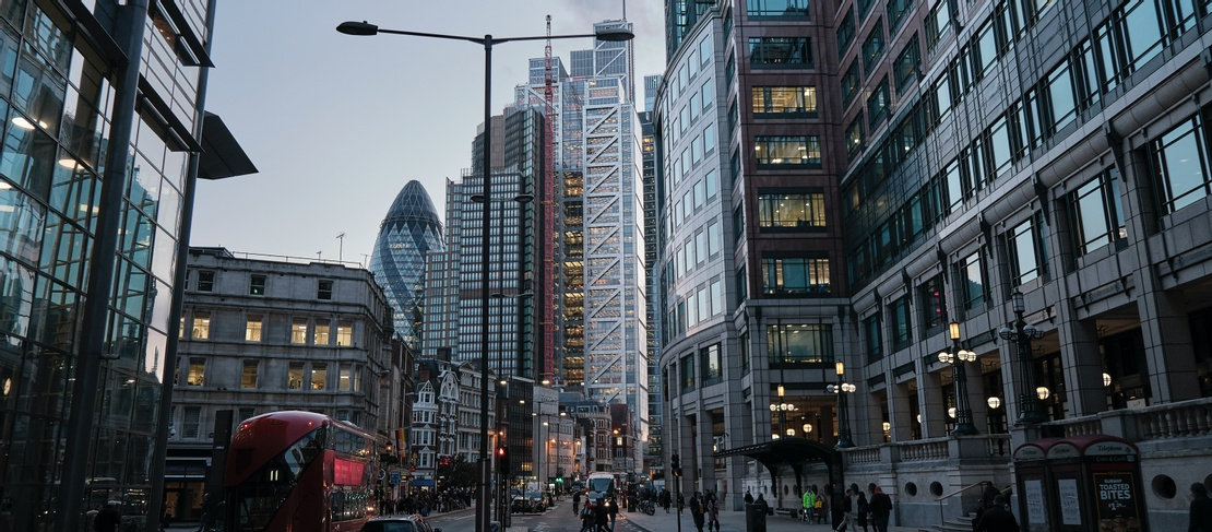 City of London road with skyscrapers imposing along skyline and traffic in foreground. Image is dark and taken in evening dusk