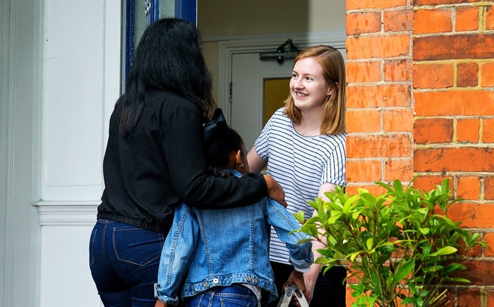 A smiling woman with red hair greets a mother and her daughter as she opens the door