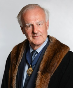 Peregrine looks into the camera, wearing a faux fur trimmed black robe and a badge of the MT crest around his neck