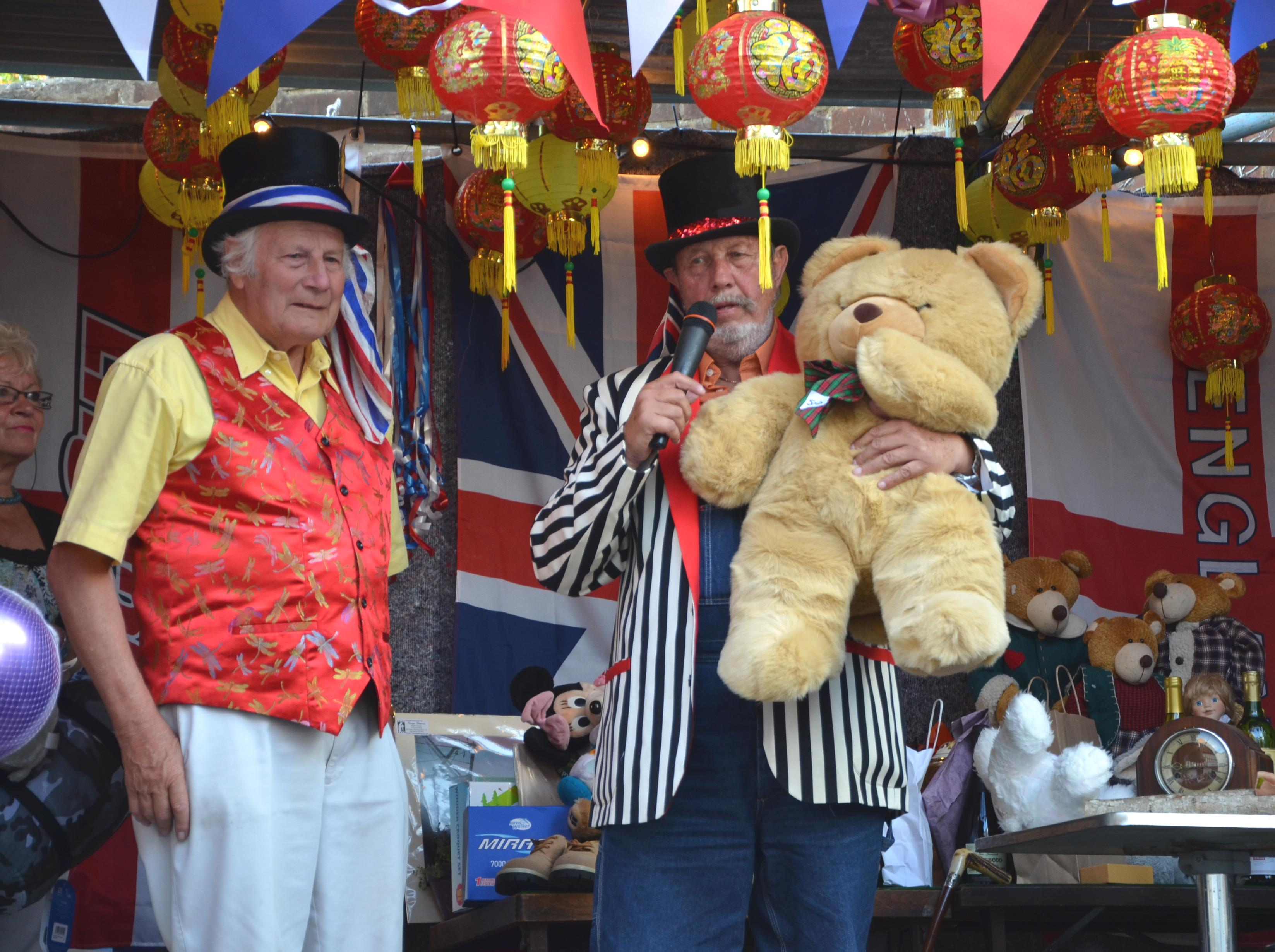 Ian  Porter and Deeday White on stage at Reeves corner, auctioning a teddy bear, donated for the auction.
