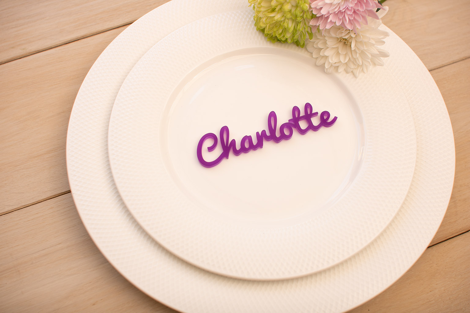 a purple acrylic wedding place name on a white plate.