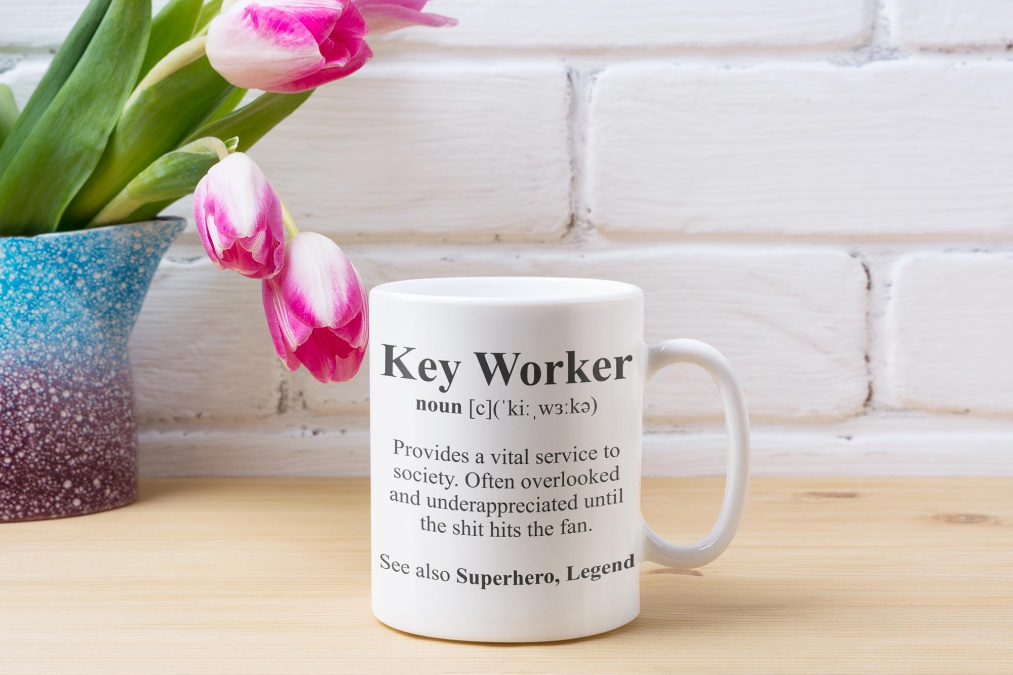 a key worker mug on a desk with flowers