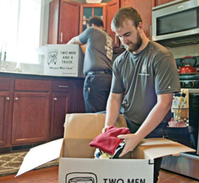 two men and a truck removal employees packing boxes