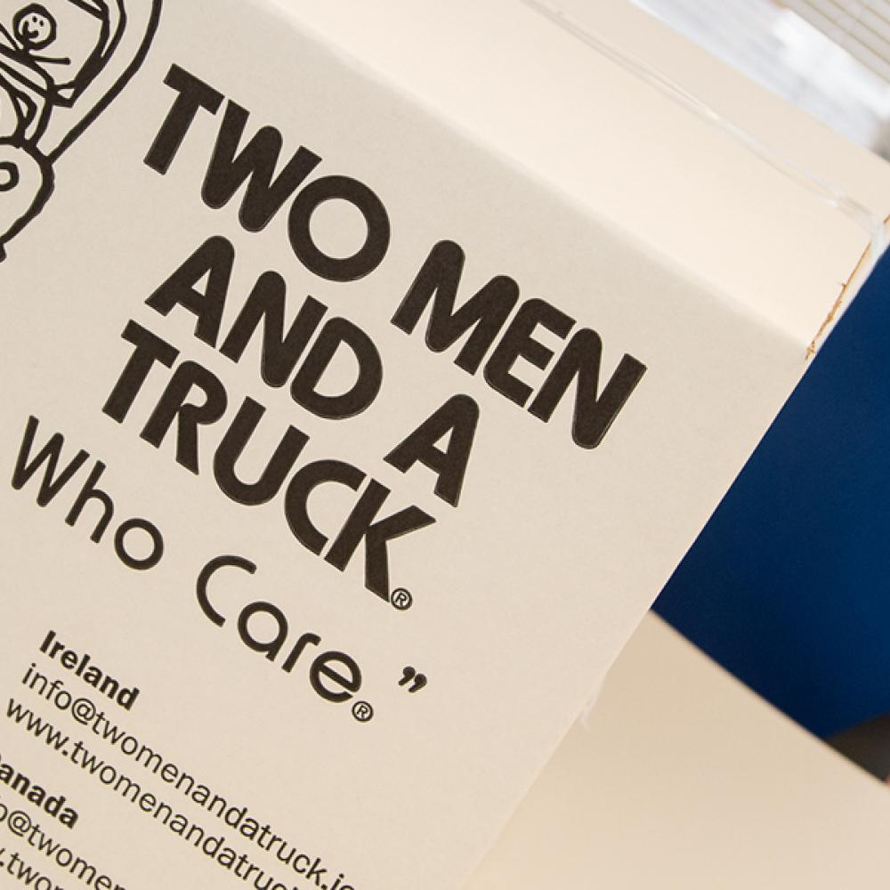 """White Two Men and a Truck box with the slogan """"Movers Who Care"""""""
