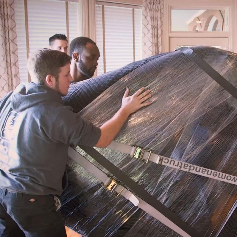 removal experts moving a piano