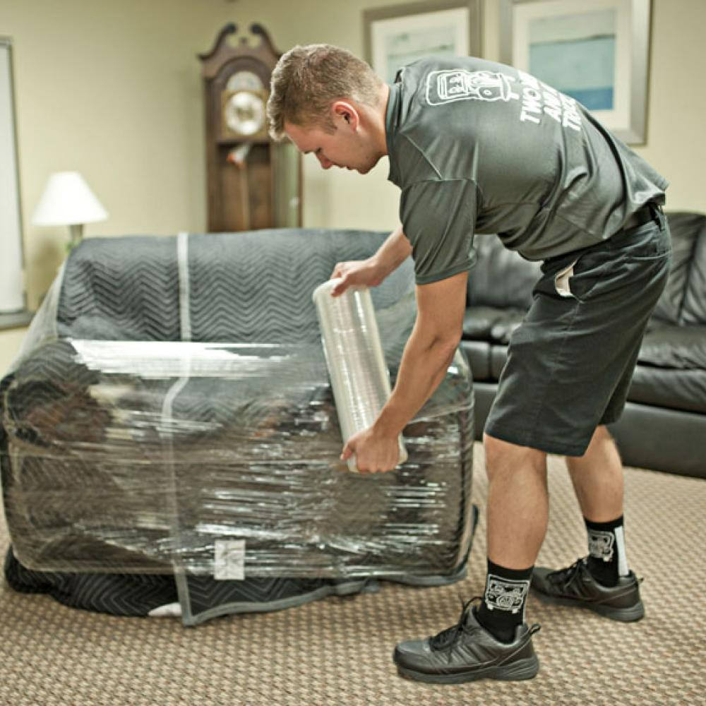 removal expert protecting furniture with stretch wrap and padding