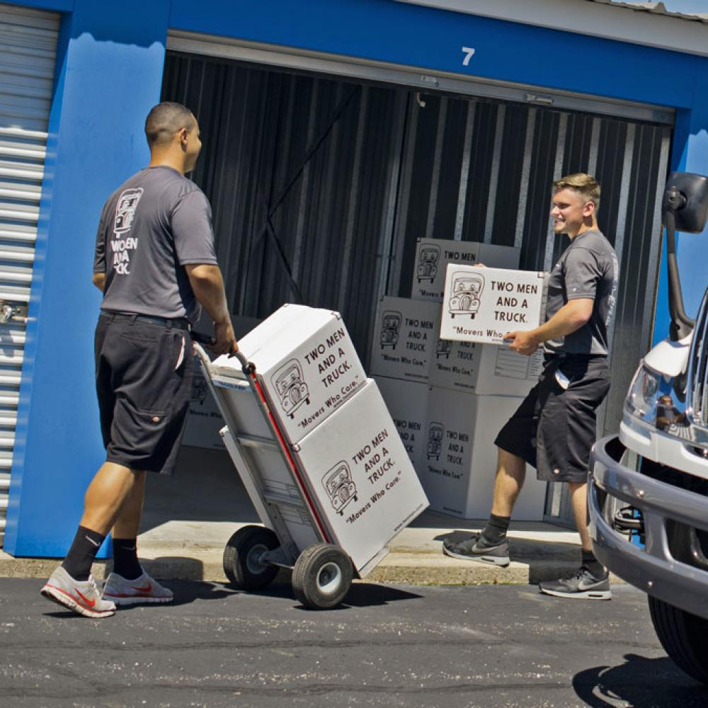 removal professionals carrying boxes into a storage locker