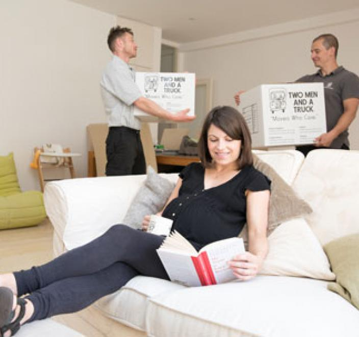 woman relaxing while movers work in the background