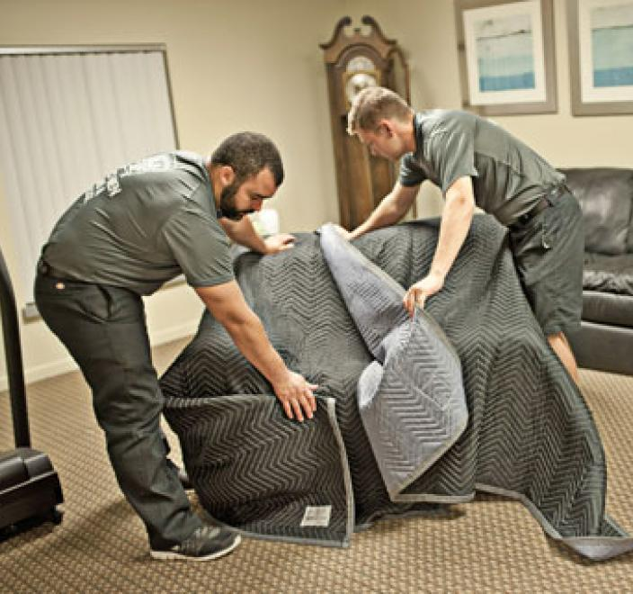 two removal experts wrapping a chair