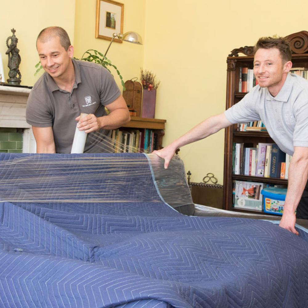 removal experts wrapping a chair with protective padding