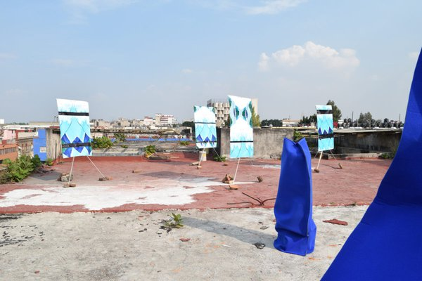4 Claire Price_Rooftop sculpture installation (untitled)_2018_Plastic banners with digital impression, bricks and flatpack alumninium stands_ Neoprene, stepladder, wooden stall, water butt.jpg