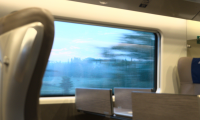 Photograph inside a train with a motion blurred view out the window