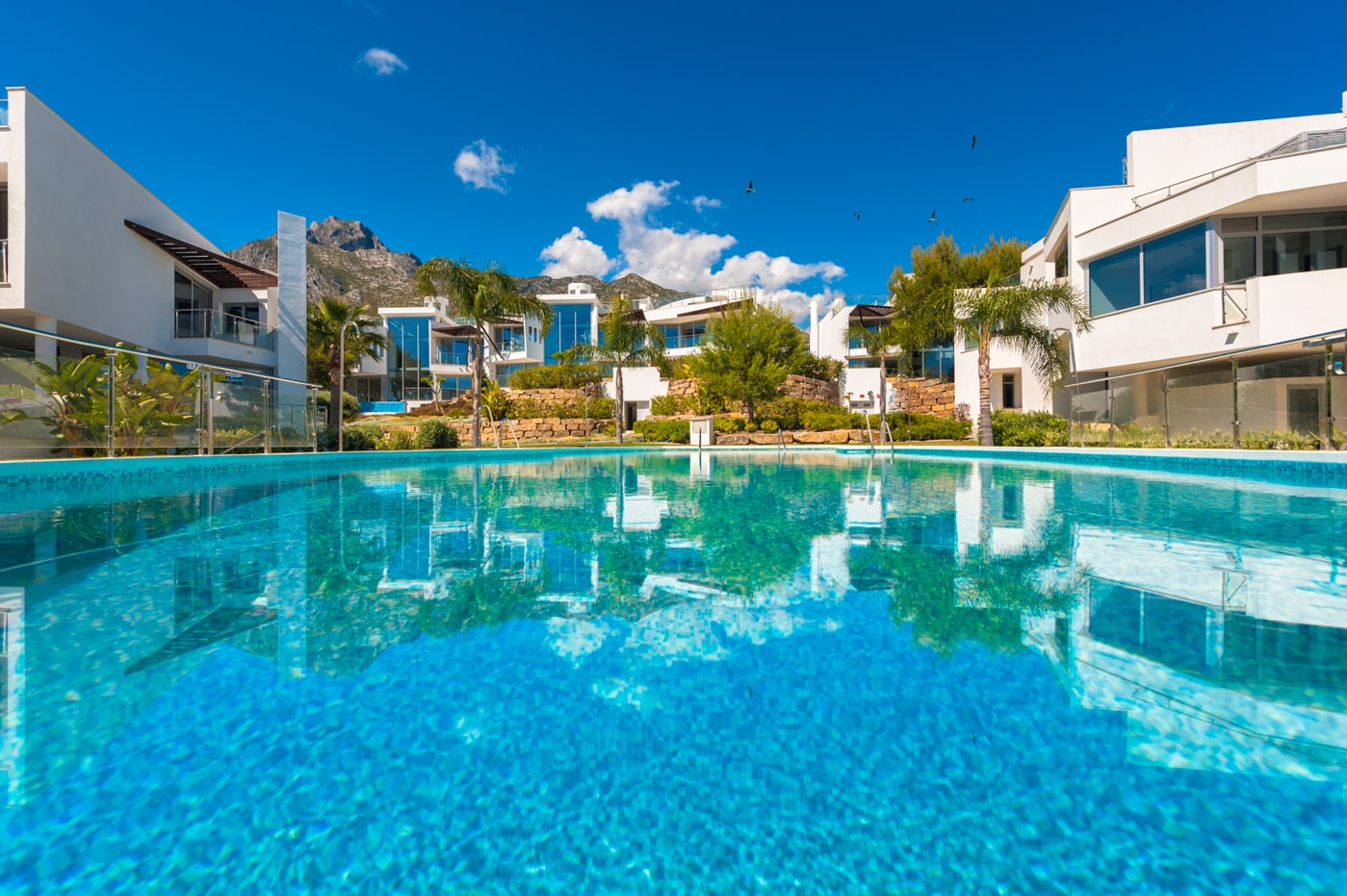 spanish villa with an infinity pool over looking the meditaranean sea surrounded by sun loungers on wooden decking