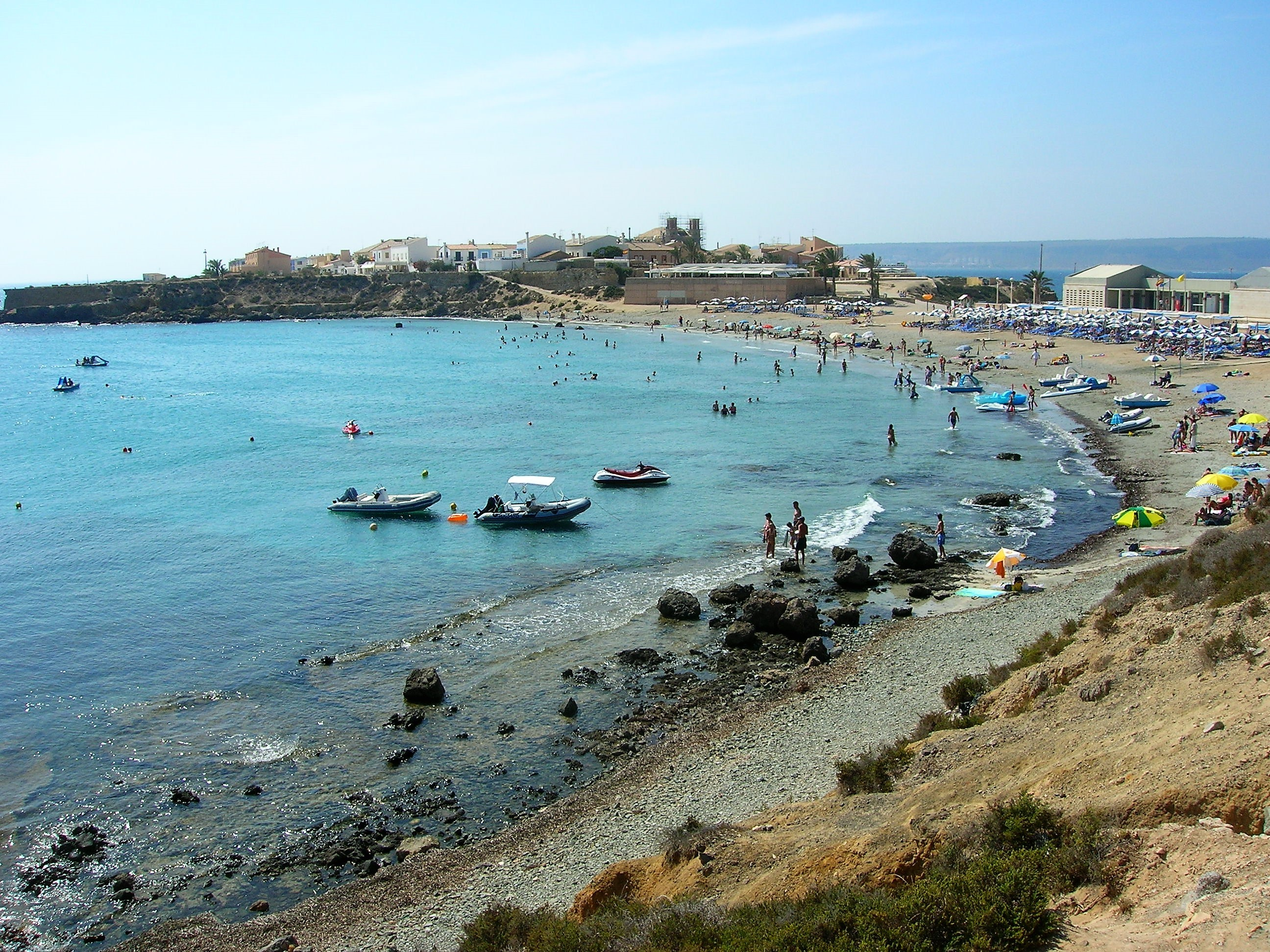 Image of a very busy isla tabarca in alicante. There is a beach with a lot of people and children, there are people swimming in the blue sea and more people sunbathing on the beach on towels, under umbrellas and some people are also having a picnic