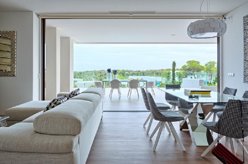 inside of luxury villa in spain, there is a large corner white colored softa to the left and a 6 seating dining table to the right. Behind these are large patio doors that open out onto a patio area with a 6 seatng dining table
