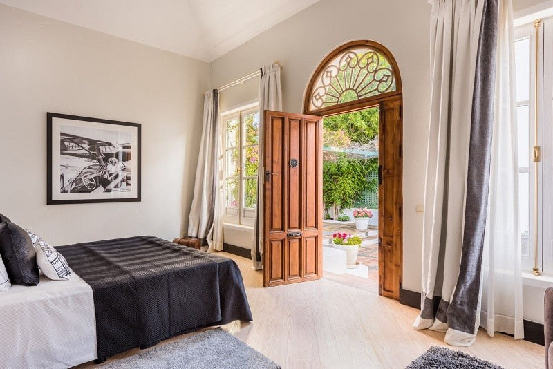 traditional style spanish bedroom with a large wooden door opening out onto a patio. French windws are on either side of the door. a double bed sits in the middle of the room.