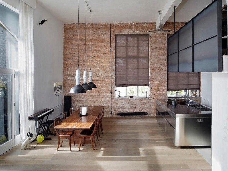 new york style loft with brick wall. open plan steal themed kitched with 8 seater wooden dining table and keyboard