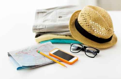 straw hat and sunglasses on top of 3 pairs of folded shorts