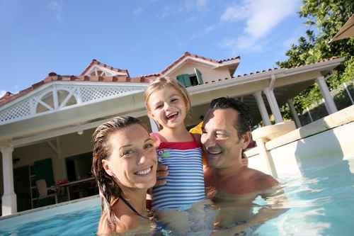 Dad, Mum and their daughter happy in swimming pool infront of villa