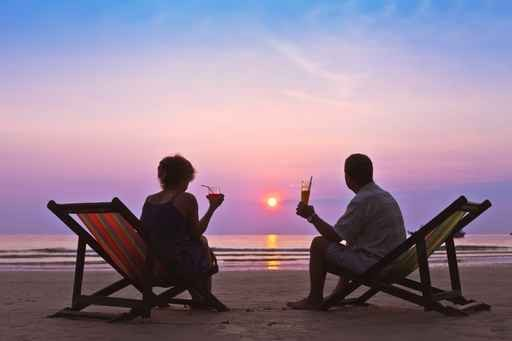 man and woman sat on deckchairs on beach at night watching the sunset