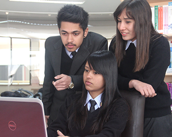 Students standing round a laptop
