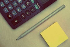 Photo of a calculator, pen and post-it note