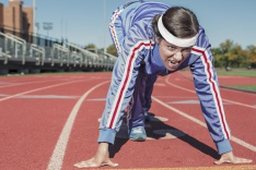 Woman on the starting blocks of a running track
