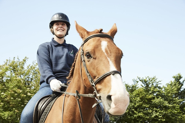 female equine student riding a horse