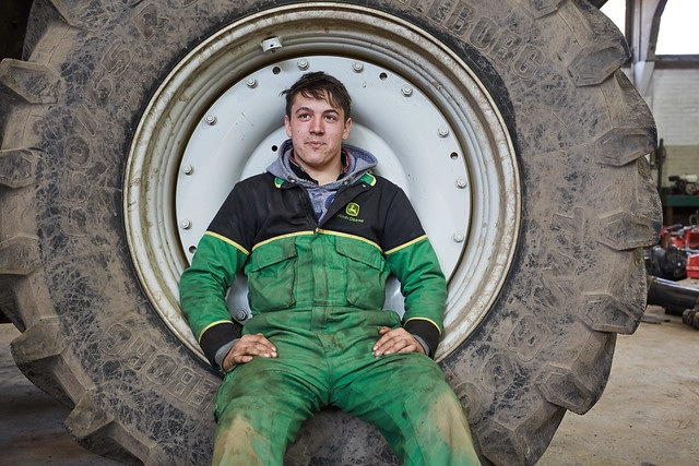 male land based student sat in tractor wheel