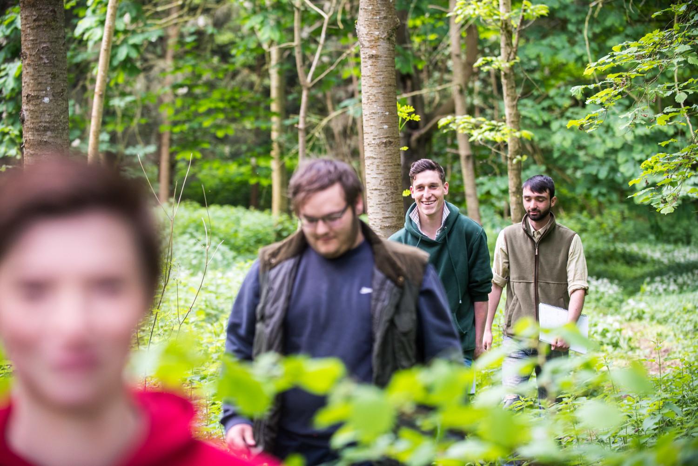 four students walking through woodland area