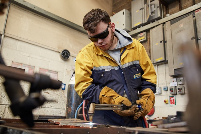 male welding student working