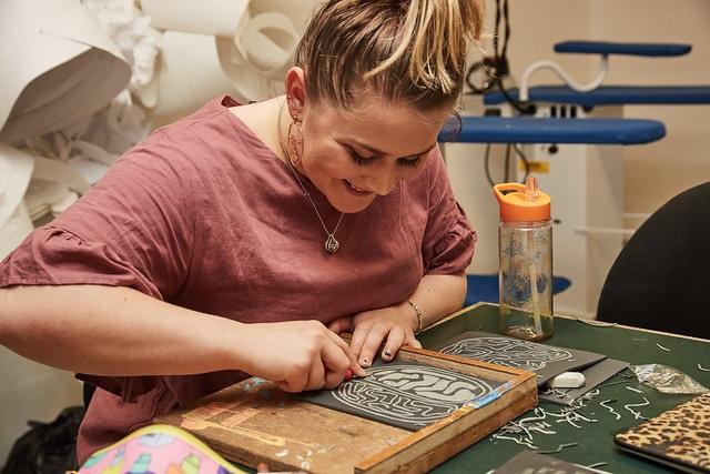 female art student sat down drawing