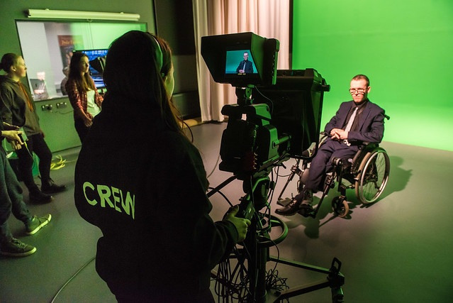 student filming male in wheelchair in front of green screen
